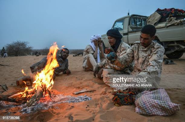 TOPSHOT Militants of The Movement for the Salvation of Azawad sit as they brew tea at a waypoint while patrolling along the MaliNiger border in the...