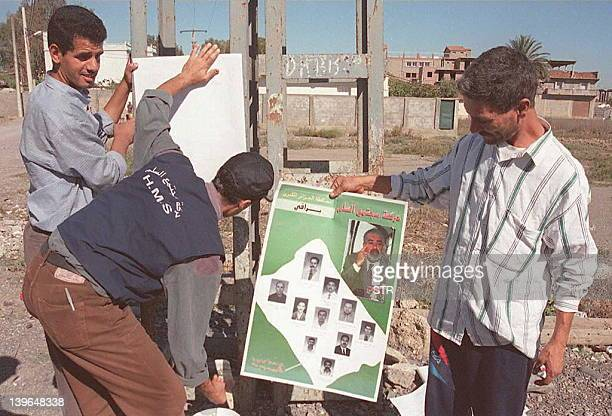 Militants of the Movement of Society for Peace exHamas stick electoral placards in Bentalhasome 20 kilometers outside Algiers 18 October in...