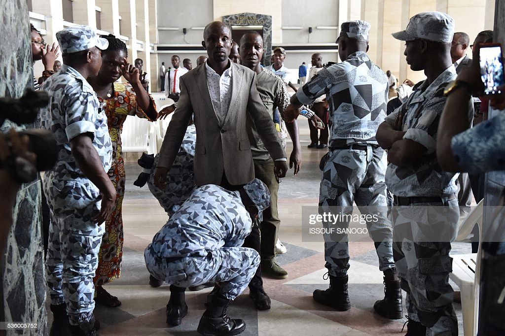 Militaries control people prior to enter the courtroom to attend Ivory Coast's former first lady trial on May 31, 2016 in Abidjan. Simone Gbagbo goes on trial for crimes against humanity in what many see as a litmus case for justice in the west African country. The hearings into the 66-year-old's role in post-election carnage in 2010 is expected to last a month with 32 witnesses testifying. / AFP / ISSOUF