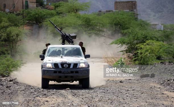 A militarised pickup truck loaded with a machinegun carries Yemeni tribesmen from the Popular Resistance Committee supporting forces loyal to Yemen's...