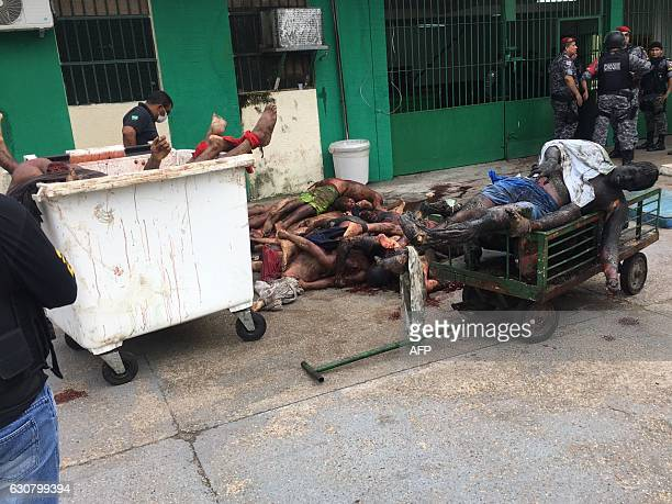CONTENT PM militarized police officers collect the bodies of inmates killed during a riot at the Anisio Jobim Penitentiary Complex Compaj 8km from...