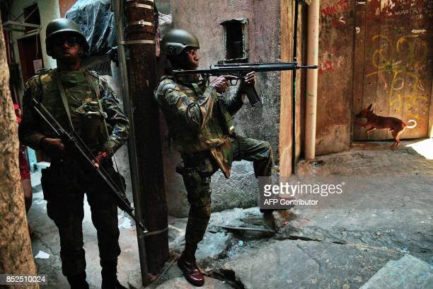 PM militarized police personnel in combat gear take position in an alley of the Rocinha favela in Rio de Janeiro Brazil on September 23 2017 Although...