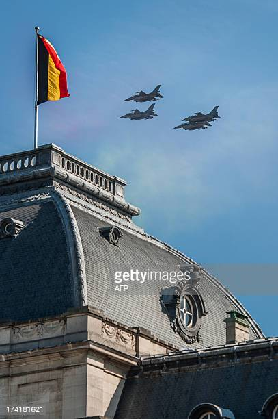 Military aicrafts fly over the Belgian Royal Palace as part of a military parade on the Belgian National Day on July 21 in Brussels. King Philippe of...