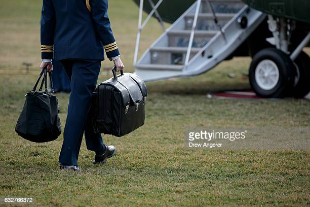 A military aide carries the alleged 'football' a case with the launch codes for nuclear weapons toward Marine One as US President Donald Trump...