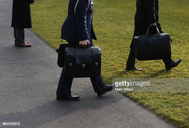 Military aide carries the nuclear football as he walks toward Marine One to depart with U.S. President Donald Trump., on December 2, 2017 in...