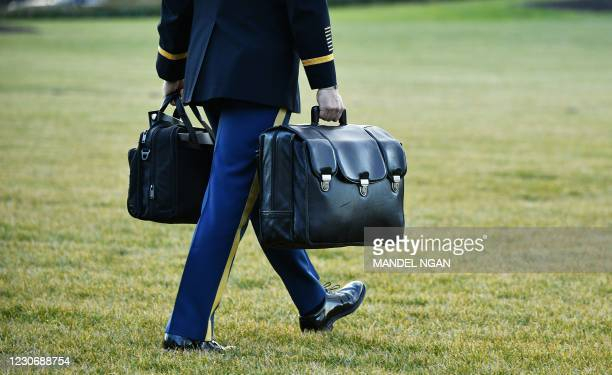 "Military aide carries the nuclear ""football"" with the equipment and nuclear codes to Marine One after US President Donald Trump and First Lady..."