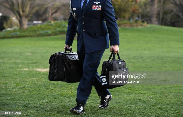 Military aide carries the presidents nuclear football in his right hand as US President Donald Trump returns to the White House, on March 31, 2019 in...