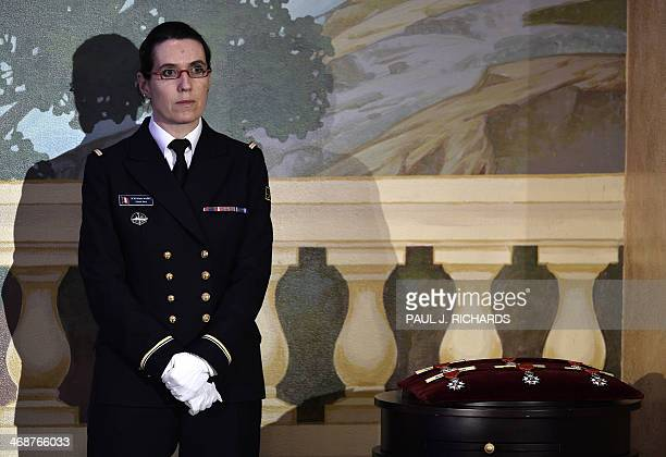 A military aide waits on the sidelines with six medals of the French Legion of Honor as French President Francois Hollande addresses the audience...
