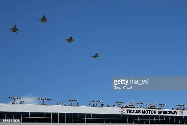 Military aircraft perform a flyover in the 'missing man formation' prior to the Monster Energy NASCAR Cup Series O'Reilly Auto Parts 500 at Texas...