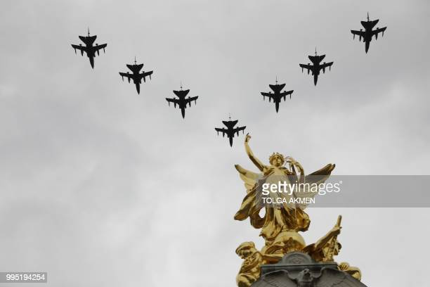 Military aircraft take part in a flypast over the Queen Victoria Memorial on the Mall outside Buckingham Palace in London on July 10 2018 to mark the...