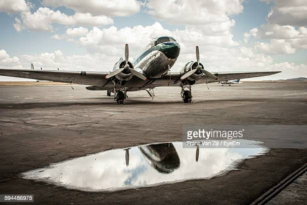 Military Airplane On Runway Against Cloudy Sky
