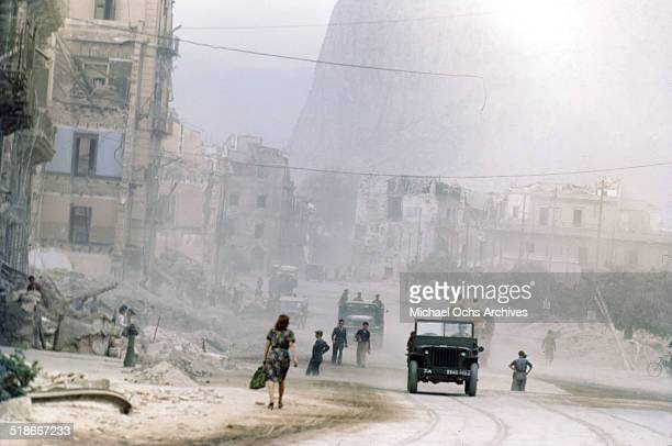 Military and locals walk in the street 5 days after winning the campaign 'Operation Husky' in Palermo Sicily Italy