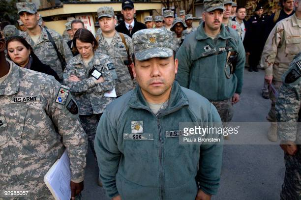 S military and NATO forces pray during a moment of silence taking part in a Veterans Day ceremony at Camp Eggers November 11 2009 in Kabul...