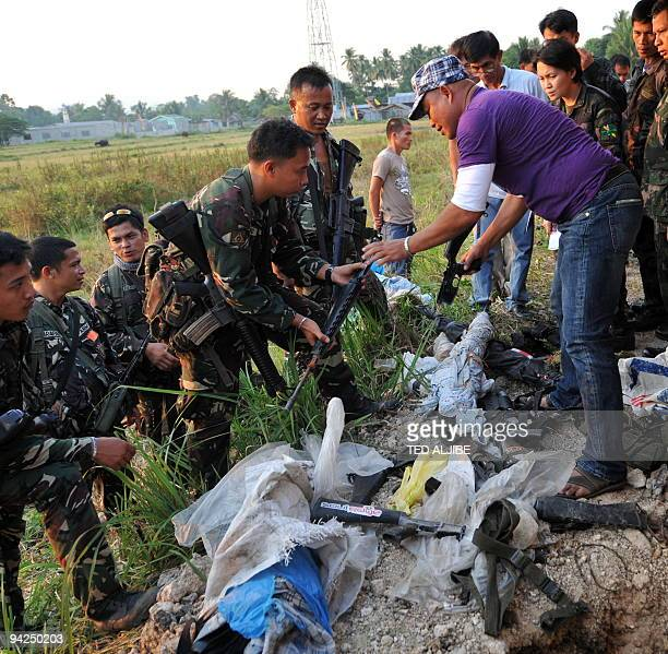 Military and police investigators examine a cache of arms unearthed at the back of the municipal hall of Ampatuan in the southern province of...