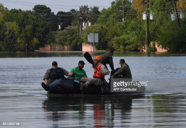 Military and State Troopers help evacuate a man beside the spillway area of the Barker Reservoir in the Coldine are a after Hurricane Harvey caused...