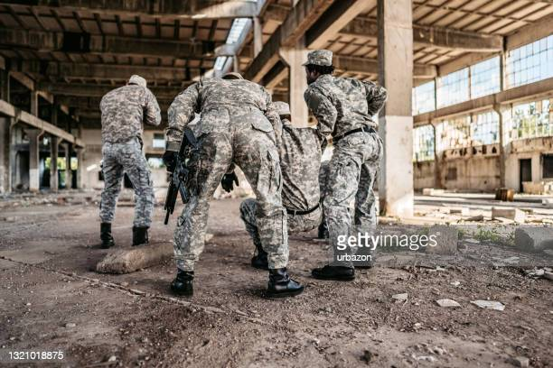 military assault team extracting wounded soldier - military invasion stock pictures, royalty-free photos & images