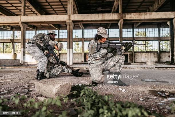 military assault team extracting wounded soldier - military attack stock pictures, royalty-free photos & images