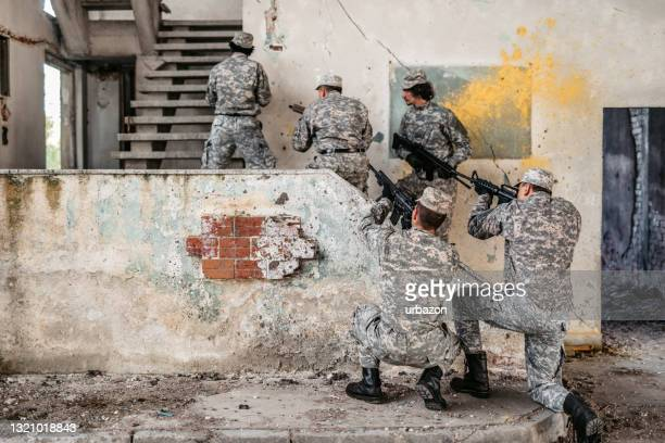 military assault team stalking on staircase in abandoned building - military attack stock pictures, royalty-free photos & images