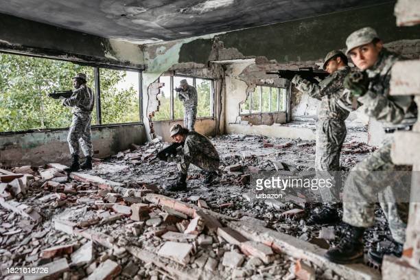 military assault team stalking through corridor in abandoned building - military attack stock pictures, royalty-free photos & images