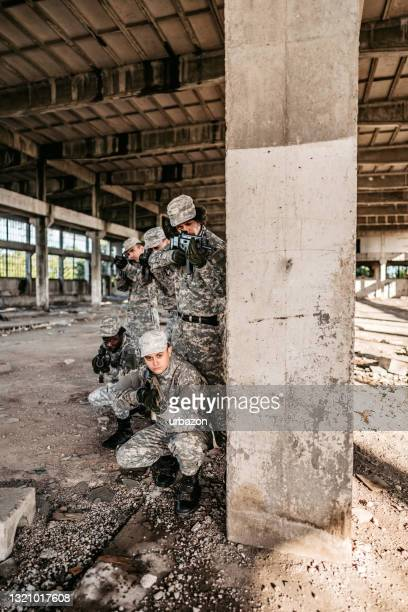military assault team taking cover in abandoned building - military attack stock pictures, royalty-free photos & images