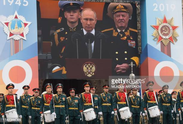A military band stands in front of a screen broadcasting President Vladimir Putin's speech during the Victory Day military parade at Red Square in...