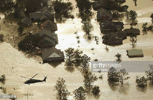S military Black Hawk helicopter flies over partially submerged homes in Hurricane Isaac's flood waters on August 31 2012 in Braithwaite Louisiana...