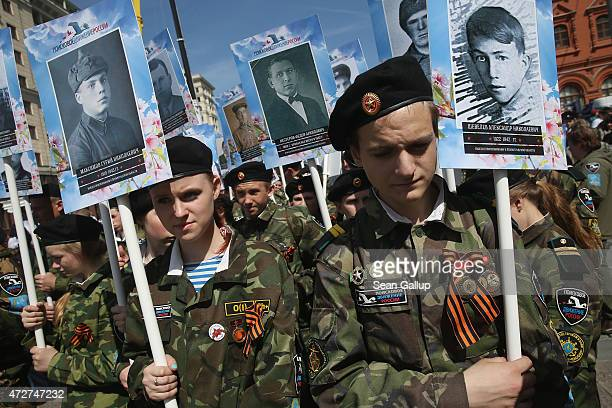Military cadets hold the portraits of young Soviets killed during World War II before a commemoration march on Red Square to as part of Victory Day...