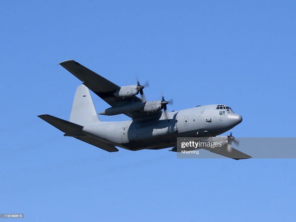 military cargo airplane Lockheed C130 Hercules flying in blue sky : Stock Photo