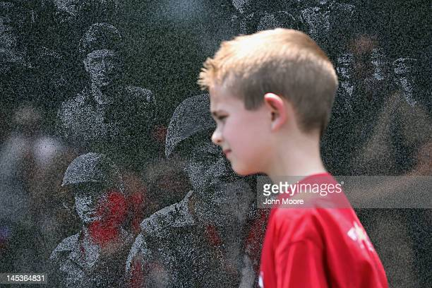 A military child grieving the death of a parent visits the Korean War Memorial as part of the TAPS Good Grief Camp on May 26 2012 in Washington DC...