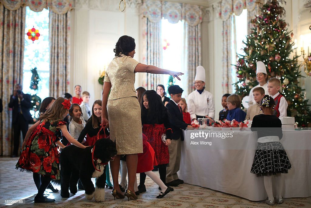 Military children pat the first family's Portuguese Water Dog Bo as U.S. first lady Michelle Obama hosts an event to preview the 2012 White House holiday decorations November 28, 2012 at the White House in Washington, DC. The first lady welcomed military families, including Gold Star and Blue Star parents, spouses and children, to the White House for the first viewing of the 2012 holiday decorations. The theme for the White House Christmas 2012 is 'Joy to All.'