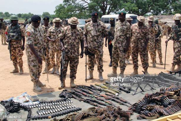 Military commanders inspect arms and ammunitions recovered from Boko Haram jihadists on display at the headquarters of the 120th Battalion in Goniri...