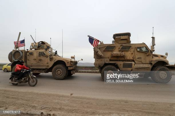 Military convoy drives on the outskirts of the Kurdish-controlled northern Syrian city of Qamishli on February 12, 2020. - The US-led coalition said...