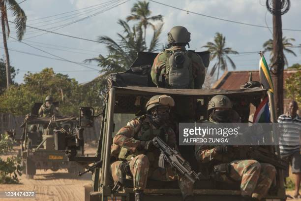 Military convoy of South Africa National Defence Forces rides along a dirt road in the Maringanha district in Pemba on August 5, 2021. - The Southern...