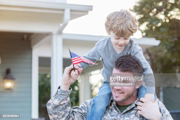 Military dad carries son on shoulders