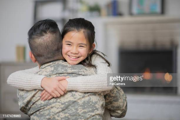 military dad hugging his young daughter - family politics stock pictures, royalty-free photos & images
