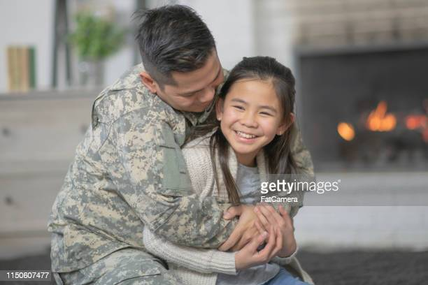military dad hugging his young daughter - filipino family reunion stock pictures, royalty-free photos & images