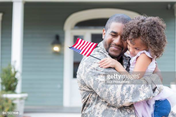 Military dad hugs preschool age daughter