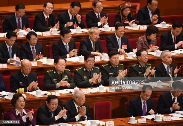 Military delegates including Zhang Yang the director of the state's Central Military Commission's political department applaud Premier Li Keqiang's...