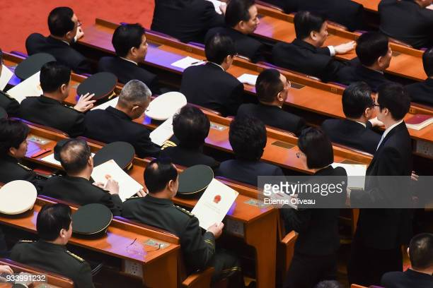 Military delegates receive their ballots from staff members before the vote during the seventh plenary session of the 13th National People's Congress...
