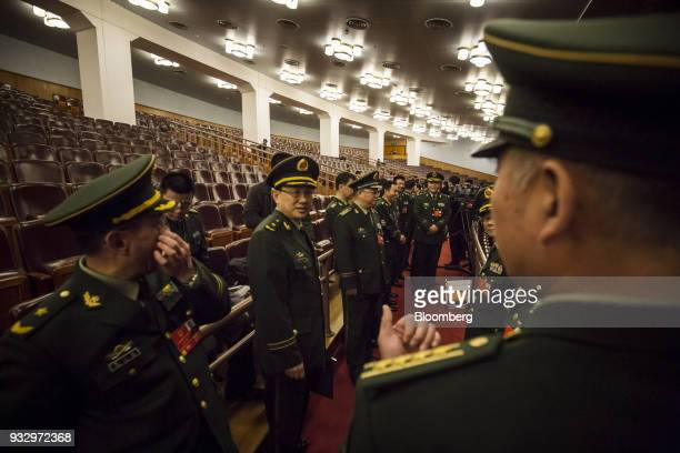 Military delegates stand ahead of a session during the first session of the 13th National People's Congress at the Great Hall of the People in...