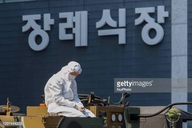 Military disinfect staff wait for COVID9 check vehicles at COVID19 drive trough check post in Daegu, South Korea. South Korea recorded daily new...