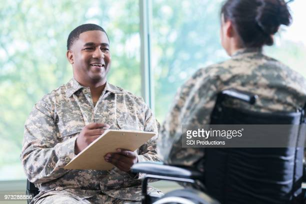 military doctor talks with patient in wheelchair - military doctor stock photos and pictures