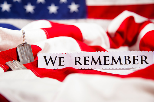 Military dog tags beside We Remember note. American flags. Patriotism. 470732308
