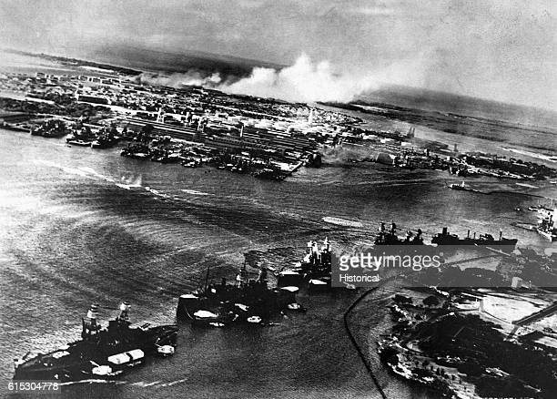 Military facilities and ships at Pearl Harbor burn during a Japanese attack on December 7 1941