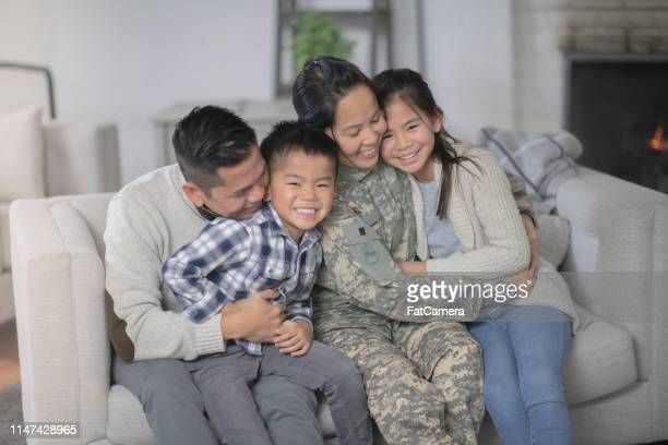 military family sitting on couch - filipino family reunion stock pictures, royalty-free photos & images