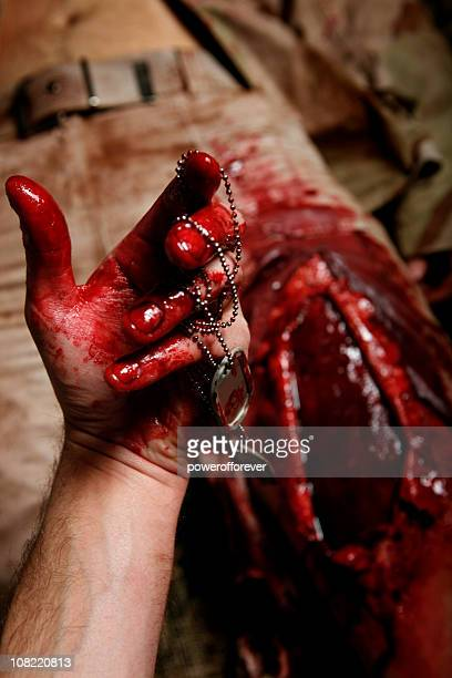 military field medic recovering dog tags from fallen soldier - wounded soldier stock photos and pictures