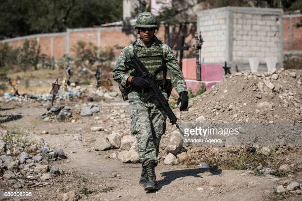 Military forces take security measures as forensic medical officials start work of exhumation on mass grave in the town of Jojutla Morelos Mexico on...
