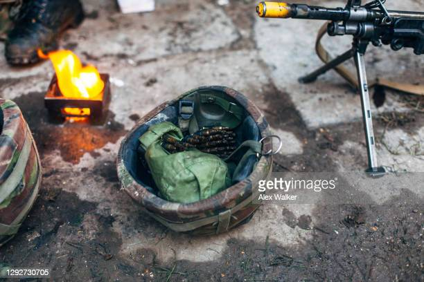military forward operating base with light machine gun and helmet as well as fire. - training grounds stock pictures, royalty-free photos & images