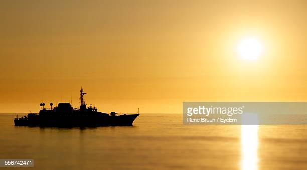 Military Frigate Sailing On Sea At Sunset