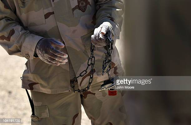 A US military guard caries handcuffs and shackles before moving a detainee inside the US detention center for enemy combatants on September 16 2010...